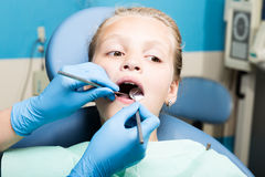 Gelukkig meisje met open mond die tandbehandeling ondergaan bij kliniek Tandarts die gecontroleerd en tanden genezen een kind Stock Fotografie