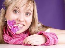 Gelukkig meisje met orchidee in mond Royalty-vrije Stock Foto's