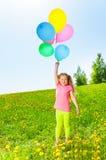 Gelukkig meisje met vliegende ballonstribunes op gras Royalty-vrije Stock Afbeelding
