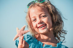 Gelukkig meisje met zeester Stock Foto