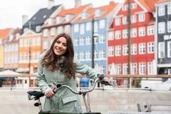 Gelukkig meisje op fiets met mooie gekleurde oude gebouwen op achtergrond Royalty-vrije Stock Foto's