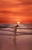 Gelukkig meisje op het strand bij zonsondergang Royalty-vrije Stock Afbeelding