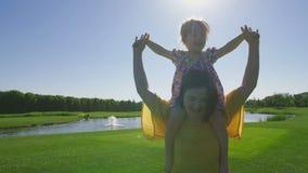 Gelukkig meisje op moeder` s schouders die op weide lopen stock footage