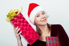 Gelukkig meisje in santahoed met giftdozen Stock Foto