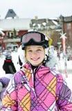 Gelukkig meisje in skihelm bij de wintertoevlucht stock fotografie