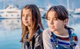 Gelukkig meisje twee die en de camera glimlachen bekijken Stock Afbeelding