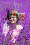Gelukkig meisje in violette bloemen Stock Foto