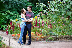 Gelukkig meisje in wapens van haar vriend onder bloemen Royalty-vrije Stock Afbeeldingen