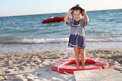 Gelukkig meisje in zeemanshoed op strand Stock Afbeeldingen