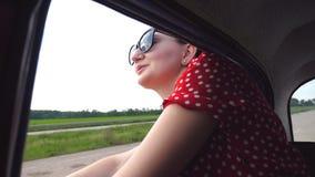 Gelukkig meisje in zonnebril die uit retro autoraam leunen en van reis genieten Aantrekkelijke jonge vrouw die uit zich het beweg stock videobeelden