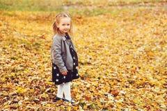 Gelukkig meisjeportret in openlucht Autumn Time Weinig blondy meisje in modieuze leerlaag en kleding bij de herfstpark gelukkig royalty-vrije stock fotografie