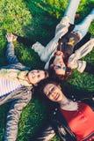 Gelukkig meisjes het liggen hoofd - - hoofd op groen gras Royalty-vrije Stock Fotografie