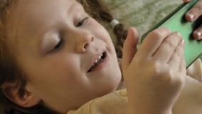 Gelukkig meisjeskind met blond haar en vlechten, liggend op de bank, die de telefoon, het glimlachen, portret met behulp van stock videobeelden