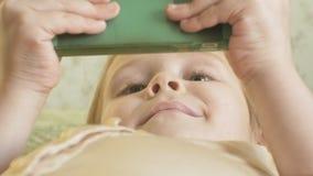 Gelukkig meisjeskind met blond haar en vlechten, liggend op de bank, die de telefoon, het glimlachen, portret met behulp van stock video