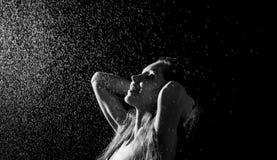 Gelukkig meisjesportret en bespattend water in haar gezicht mooi vrouwelijk model op zwarte achtergrond Stock Foto