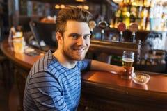 Gelukkig mens het drinken bier bij bar of bar Stock Foto's