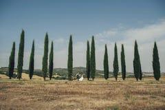 Gelukkig modieus glimlachend paar die en in Toscanië, Ita lopen kussen stock afbeeldingen