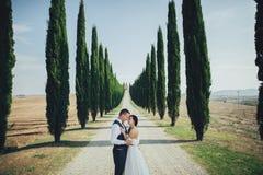 Gelukkig modieus glimlachend paar die in Toscanië, Italië op hun lopen stock afbeeldingen