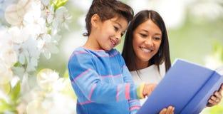 Gelukkig moeder en dochterlezingsboek stock foto