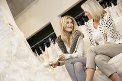 Gelukkig moeder en dochterzittingsschoeisel in bruids opslag Royalty-vrije Stock Fotografie