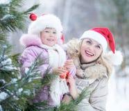 Gelukkig moeder en jong geitje in de hoeden van de Kerstman met Royalty-vrije Stock Afbeeldingen