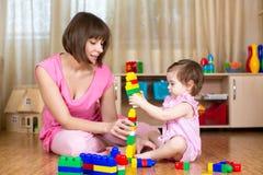 Gelukkig moeder en jong geitjespel met speelgoed thuis Royalty-vrije Stock Foto's
