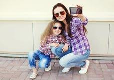 Gelukkig moeder en kind die zelf-portret op smartphone nemen Stock Afbeeldingen