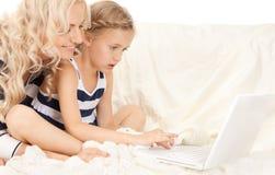 Gelukkig moeder en kind met laptop computer Stock Afbeelding