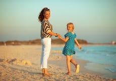 Gelukkig in moeder en kind op zeekust bij zonsondergang royalty-vrije stock fotografie