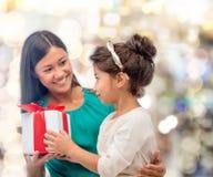 Gelukkig moeder en kindmeisje met giftdoos Stock Foto's