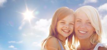 Gelukkig moeder en kindmeisje over zon in blauwe hemel Stock Foto