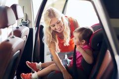 Gelukkig moeder vastmakend kind met autoveiligheidsgordel royalty-vrije stock fotografie