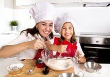 Gelukkig moederbaksel met weinig dochter in schort en kokhoed met bloemdeeg bij keuken Royalty-vrije Stock Fotografie