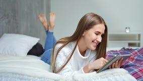 Gelukkig mooi jong meisje die van weekend genieten die op bed in slaapkamer liggen die tabletpc met behulp van stock footage