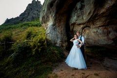 Gelukkig mooi jonggehuwdepaar Glimlachende bruidegom die de charmante bruid terug op de groene bergen koesteren Stock Afbeeldingen