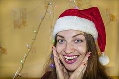Gelukkig mooi meisje die in een rode Kerstmishoed glimlachen Stock Afbeeldingen