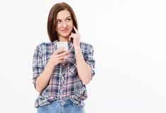 Gelukkig mooi meisje die haar apparaat op witte achtergrondexemplaarruimte met behulp van, beeld van een glimlachende donkerbruin royalty-vrije stock afbeeldingen