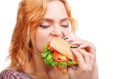 Gelukkig mooi meisje met de smakelijke sappige hamburger van de hamburgersandwich in handen die klaar te eten geïsoleerd op een w stock afbeeldingen