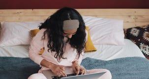 Gelukkig mooi meisje in roze pyjama's die aan een laptop zitting op het bed in het huis werken Zij glimlacht stock video