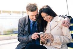 Gelukkig mooi paar die smartphone samen gebruiken Stock Afbeeldingen