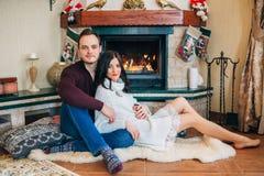 Gelukkig mooi paar in liefde dichtbij open haard het stellen bij de camera stock fotografie