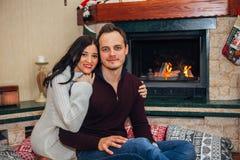 Gelukkig mooi paar in liefde dichtbij open haard het stellen bij de camera royalty-vrije stock afbeeldingen