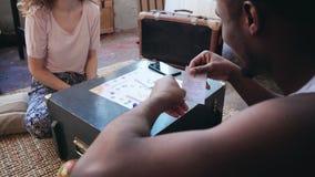Gelukkig multi-etnisch paar die in pyjama's het raadsspel op de vloer spelen De man werpt dobbelt en zet de kaart, vrouwenlach royalty-vrije stock foto