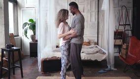 Gelukkig multi-etnisch paar in pyjama's die samen dansen Krop en vrouwenomhelzingen, dalingen op het bed en kussen Langzame Motie stock footage