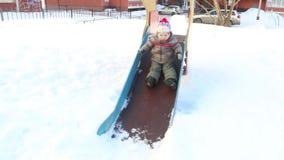 Gelukkig neer glijdt weinig jongen en het meisje gaat dichtbij hem bij de winter zonnige dag stock videobeelden