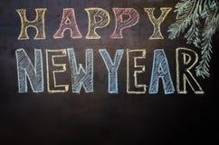 Gelukkig nieuw die jaar met krijt op een zwarte achtergrond wordt geschreven Stock Foto's