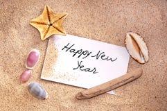 Gelukkig nieuw die jaar, op een nota in het zand wordt geschreven royalty-vrije stock foto's