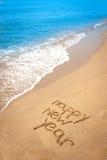 Gelukkig nieuw die jaar in zand op tropisch strand wordt geschreven stock foto's
