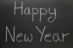 Gelukkig Nieuwjaar dat op een schoolbord wordt geschreven. Stock Afbeelding
