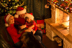 Gelukkig Nieuwjaar Familie het spelen met hun hond in Kerstmis feestelijke verfraaide woonkamer Huisdier, mensen, vakantieconcept Stock Foto